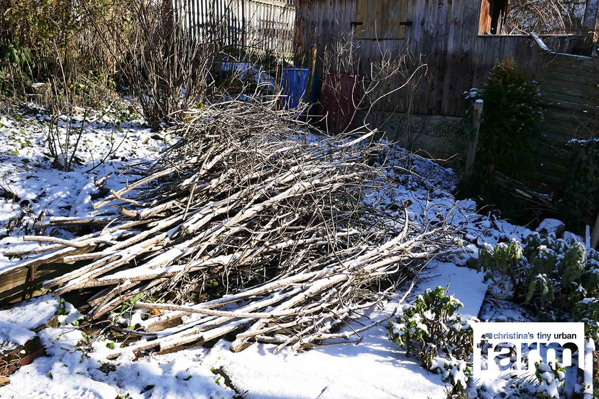 Cut off branches, covered in snow, providing shelter for small critters.